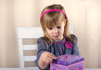 Little girl decorates the box.