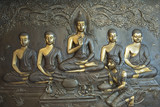 Buddha life scenes on carved metal at the temple in Thailand.