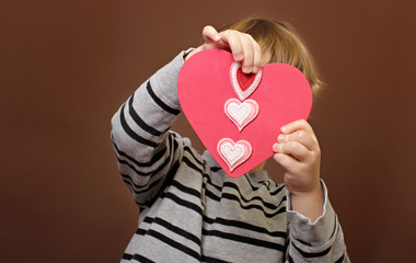 Child holding Valentine's Day Craft with Hearts
