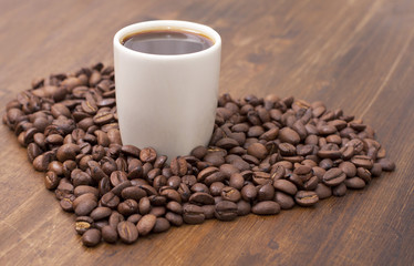 Heart of roasted coffee beans, a cup of coffee on a wooden table