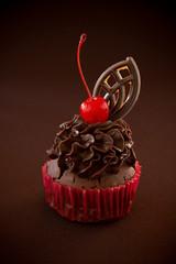 Fresh chocolate muffins with chocolate cream and cherry.