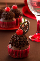 Fresh chocolate muffins with chocolate cream and cherry.