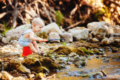 Little smiling boy fishing outdoors