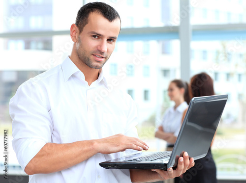 Portrait of a smart business man using laptop with colleagues