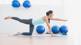 Sporty woman stretching hand and leg in fitness studio