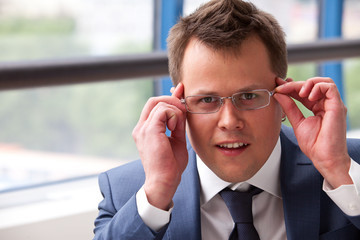 businessman adjusts his glasses