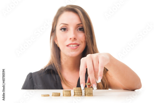 Businesswoman with stacks coins against white background.