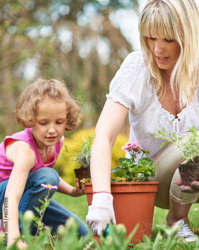 Mutter und Kind gärtnern im Garten im Sommer