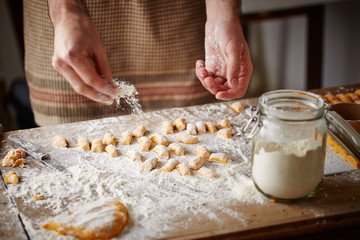 Cook preparing raw pumpking gnocchi