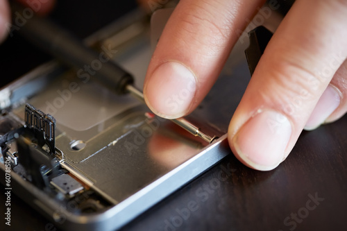 Hands fixing smartphone close-up