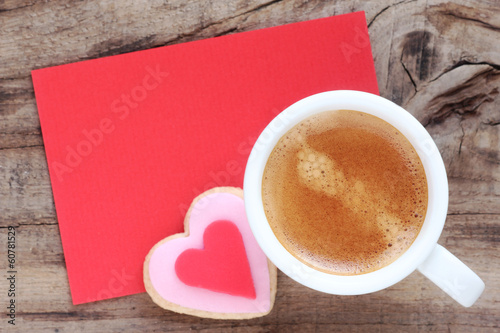 Cup of espresso coffee with a cookie and a red message card