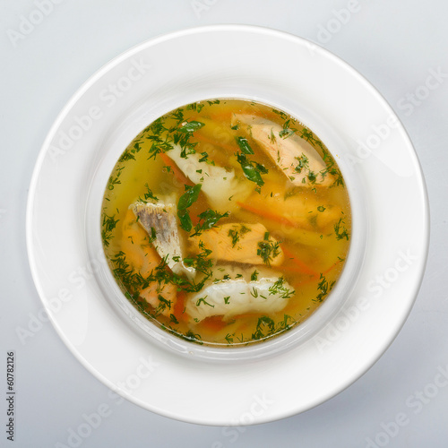 Fish soup with potato and carrots top view