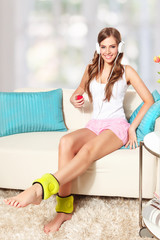 Beautiful young woman listening to music while doing leg exercis