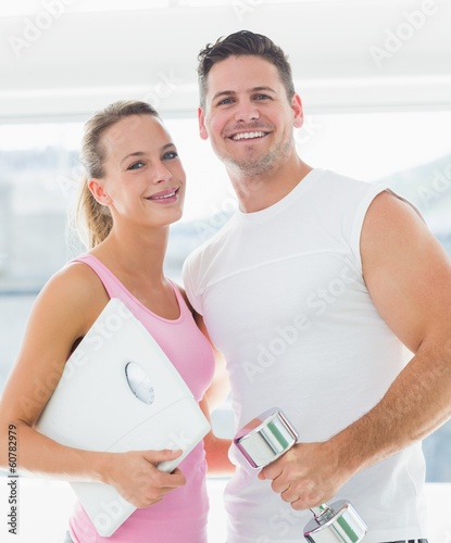 Fit couple holding dumbbell and weighing scale