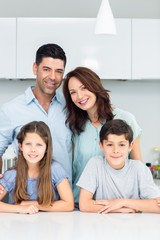 Portrait of a happy family of four in kitchen