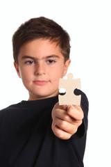 bambino mostra un pezzo di puzzle