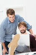zwei entspannte männer schauen auf laptop