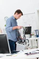 mann mit einer kiste voller kabel im büro