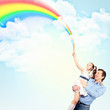 Father holding his daughter and rainbow