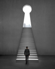 Businessman walking on stair to key shape door, city view