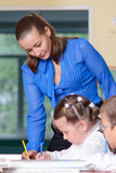 Teacher helping little schoolgirl