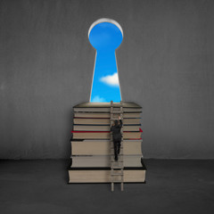 Businessman approaching books top with key shape door, blue sky