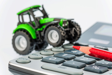 tractor, red pen and calculator