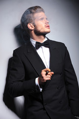fashion man in tuxedo and bow tie blowing his smoke