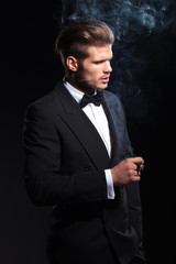 side of a fashion man in tuxedo smoking a cigar