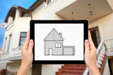 Female hands hold a tablet with drawing of apartment house on th