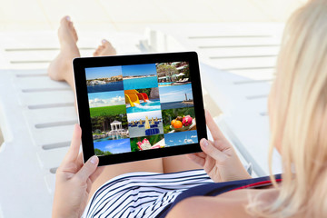 girl in a bathing suit lying on a chaise lounge with a tablet an