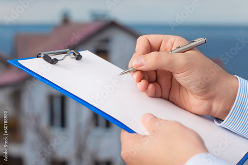 businessman signs a document on the background of an apartment b