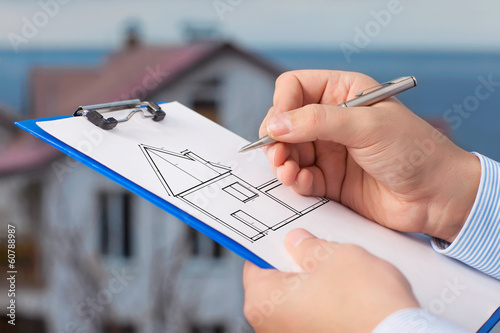 businessman  draws a drawing of a house on the background of an