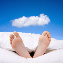two bare feet resting in bed happy