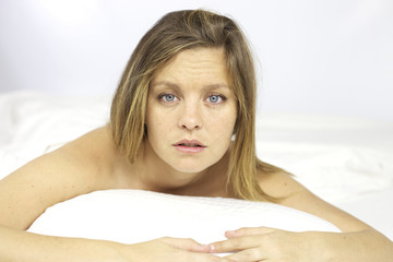 Tired young woman in bed