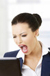 Angry businesswoman shouting on her laptop