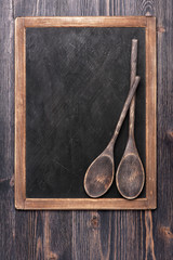 Black chalk board with old wooden spoons