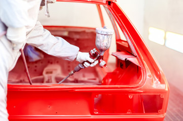 Close-up of spray paint gun with worker working on a red car