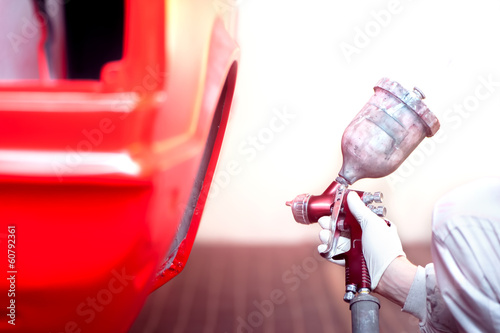 worker painting a red car or element in a special garage