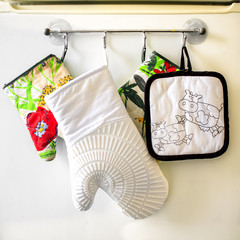 Oven gloves hanging in a row on the kitchen frige