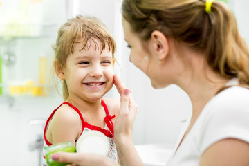 mother putting cream on her daughter's face in bathroom