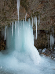 Large ice pillar stands in a cave near the icicles