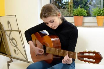 Schülerin spielt Gitarre in Musikschule