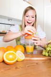 Junge Frau beim Saft pressen - Orangensaft