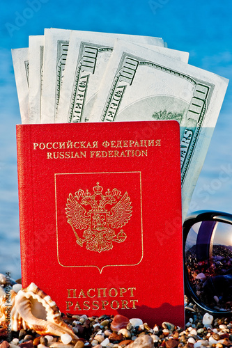 passport with dollars on the beach against the sea