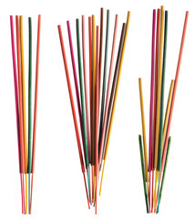 Groups of colorful incense sticks on white background