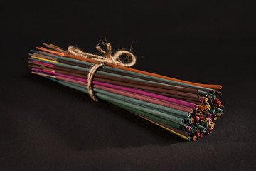 Group of colourful incense sticks on black background