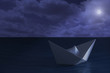 Paper boat floating in the sea at night