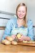 Junge Frau beim Kartoffeln schälen