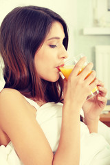 Woman in bed drinking orange juice